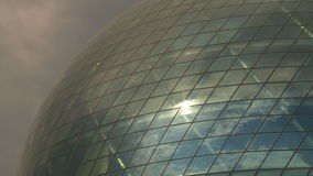 Modern sphere glass building and sunlight reflections in cloudy sky stock footage