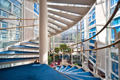 Modern spiral staircase. A modern white spiral staircase with a blue carpet in the centre of a hotel Stock Photos