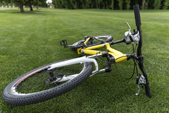 Modern sport bicycle lying on grass in park. Close up of modern sport bicycle lying on grass in park Stock Image