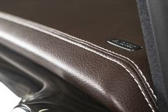 Modern sport car brown leather interior. Part of leather car cockpit details with stitching. Car detailing. Brown perforated leath stock photo
