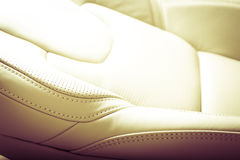 Modern sport car white leather interior. Part of  leather car seat with the unfocused car interior on the background, vintage filter Royalty Free Stock Images