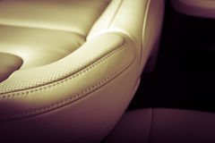Modern sport car white leather interior. Part of  leather car seat with the unfocused car interior on the background, vintage filter Royalty Free Stock Image