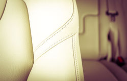 Modern sport car white leather interior. Part of  leather car seat with the unfocused car interior on the background, vintage filter Stock Photos
