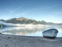 Modern sport fishing paddle boat anchored on shore royalty free stock photography