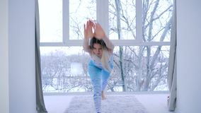 Modern sport hobby, shapely female practicing yoga near window at home. Modern sport hobby, shapely female practicing yoga near window at living room stock footage