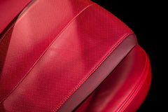 Modern sport luxury car inside. Interior of prestige modern car. Comfortable leather red seats. Red perforated leather cockpit with isolated Black background royalty free stock photography
