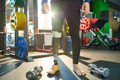 Modern sportsman with prosthetic leg. Close-up of unrecognizable modern sportsman with prosthetic leg wearing leggings standing in gym with fitness equipment royalty free stock photography