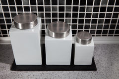 Modern square design storage jars on work surface in black and w Stock Images