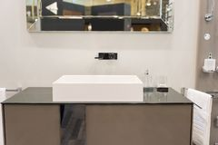 Modern square washbasin with tap mounted to wall under the mirror. Concept of home interior royalty free stock image