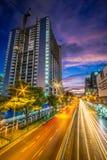 Modern stad på natten med ljusa linjer för bilar Arkivfoto