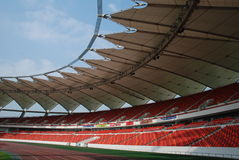 A modern stadium. An empty modern stadium with domes ,curves of red chairs,stand,and tracks Stock Photos