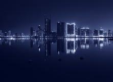 Modern stadshorisont för natt med glänsande ljus och reflexion Royaltyfri Foto