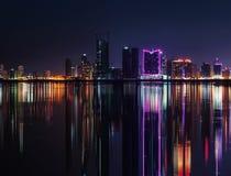 Modern stadshorisont för natt med neonljus och reflexioner Arkivbilder
