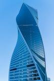 Modern stadsskyskrapabyggnad av den ovanliga (vridna) designen på blå solnedgånghimmel Royaltyfri Bild