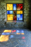 Modern stained glass windows reflecting colors. On church walls and floor Stock Photography