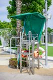 Modern stainless lifeguard chair with green roof around swimming pool. Modern stainless lifeguard  or life-saving chair with green roof around swimming pool area royalty free stock image