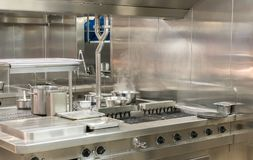 Modern stainless steel hobs in commercial kitchen. Food being cooked in commercial stainless steel kitchen in restaurant royalty free stock image