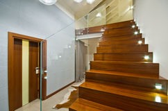 Modern stairs with glass handrail. Modern private house interior with wooden stairs and glass transparent handrail Stock Images