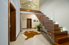 Modern stairs with glass handrail. Modern private house interior with wooden stairs and glass transparent handrail Royalty Free Stock Image
