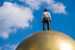 Modern statue man on ball gold. Standing looking clear blue sky in summer stock photos