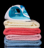 Modern steam iron and stack towels in isolation on black. Royalty Free Stock Photos
