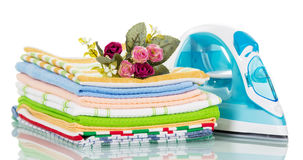 Modern steam iron and stack of towels, rose isolated. Stock Photos