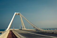 Modern steel bridge – horizontal view. White colored tower of contemporary steel bridge with light blue sky and horizon line at the background Stock Images