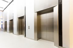Modern steel elevator all closed cabins in a business lobby or H. Otel, Store, interior, office,perspective wide angle. Three elevators in hotel lobby Royalty Free Stock Images