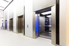 Modern steel elevator opened cabins in a business lobby or Hotel. Store, interior, office,perspective wide angle. Three elevators in hotel lobby Stock Photos