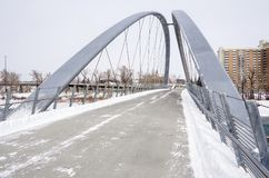 Deserted Steel Footbridge on a Snowy Day. Modern Steel Pedestrian Bridge on a Snowy Winter Day. Calgary, AB, Canada Stock Photo