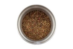 Modern steel pepper grinder with ground pepper mix isolated on white background. Closeup top view. A mix of four types of pepper. Black, white, pink, green royalty free stock photos