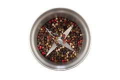 Modern steel pepper grinder with a pepper mix isolated on white background. Blade top view. A mix of four types of pepper grain. Black, white, pink, green stock image