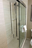 Modern Step-In Shower. A sleek looking shower stall with sliding doors, a rain head, chrome sliding bar and hand wand. Contrasting tones of beige, taupe and Royalty Free Stock Images