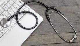 Modern stetoskop och vitbärbar dator på bakgrund royaltyfria bilder