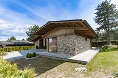 Modern stone house with well kept yard stock photography