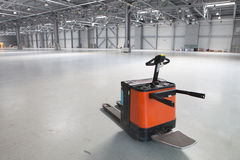 Modern storehouse. Electric forklift in large modern storehouse with some goods Stock Images