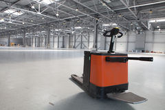 Modern storehouse. Electric forklift in large modern storehouse with some goods Stock Photos