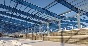 Modern storehouse construction site, the structural steel structure of a new commercial building against a clear blue