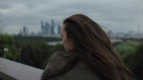 Modern storstadhorisont Tillbaka sikt av en ung härlig flicka som tycker om sikten Flickan som ångrar hennes långa hår som vänder stock video