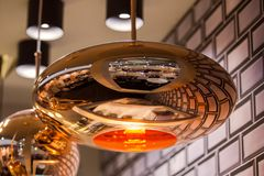 Modern streamlined mirror oval copper chandelier. Bubble metal copper shade pendant.  Stock Photos