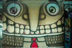 Modern street art - graffiti. On the walls of the bus station, Tel Aviv, Israel. Toothed man, from the cartoon effect lead koloboks Royalty Free Stock Images