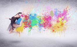 Modern street dancer jumping with colorful paint splashes. On back wall concept royalty free stock images
