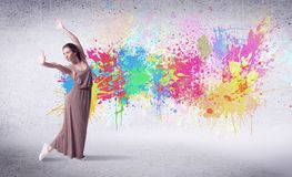 Modern street dancer jumping with colorful paint splashes. On back wall concept stock images