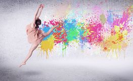 Modern street dancer jumping with colorful paint splashes. On back wall concept stock photo