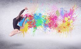 Modern street dancer jumping with colorful paint splashes. On back wall concept stock image