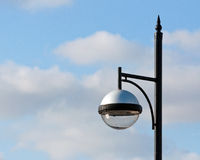 Modern street lamp. A modern street lamp against a blue and cloudy sky Royalty Free Stock Photo