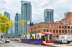 Modern streetcar on a street of Toronto. The Toronto streetcar system is the largest and the busiest light-rail system. Toronto, Canada - May 2, 2017: Modern Royalty Free Stock Photos