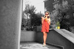 Modern student wearing bright red sunglasses waiting outside for her boyfriend. Waiting fro boyfriend. Modern beautiful pleasant student wearing bright red royalty free stock images