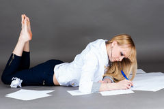 Modern student writes lying on the floor Royalty Free Stock Photos