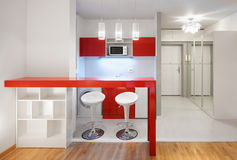 Modern studio flat or hotel kitchen in red Royalty Free Stock Images